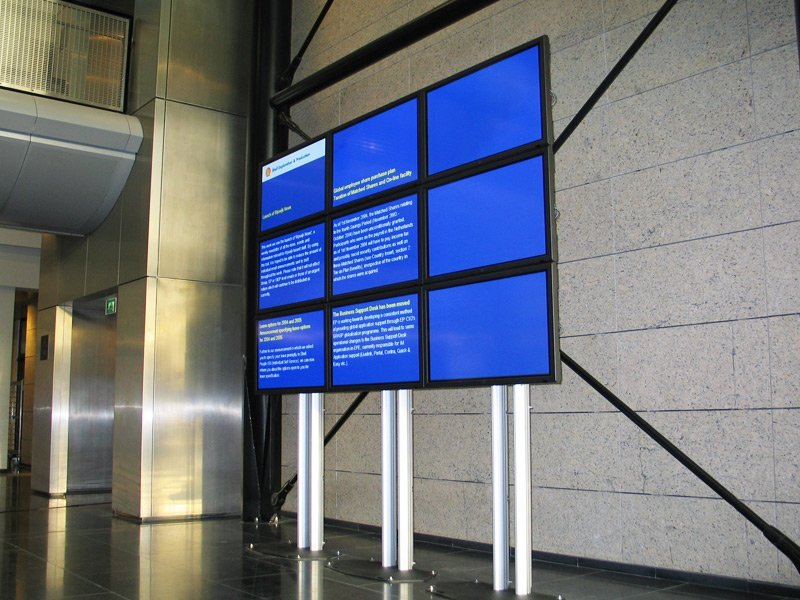 Digital Signage board showcasing a blue screen with tiny ads